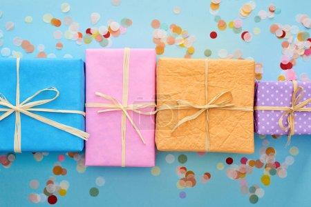 Photo pour Vue du dessus des boîtes-cadeaux emballées près de confettis sur bleu - image libre de droit