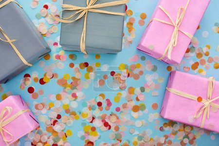 Photo pour Top view of colorful wrapped presents near confetti on blue - image libre de droit