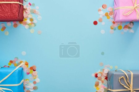 Photo for Top view of wrapped presents near colorful confetti on blue - Royalty Free Image