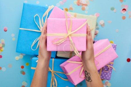 oříznutý pohled na ženu drží růžové dárkové krabice v blízkosti barevné dárky v blízkosti konfety na modré