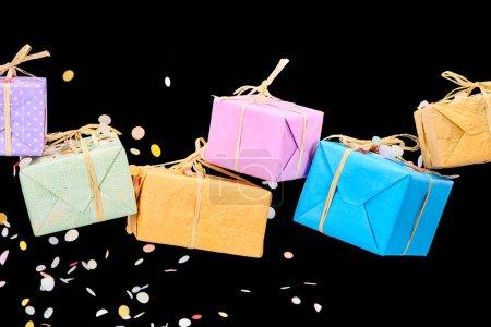Photo pour Falling confetti near colorful gifts on black - image libre de droit