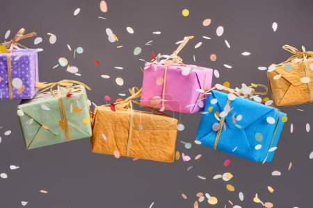 Photo for Falling confetti near colorful presents on grey - Royalty Free Image