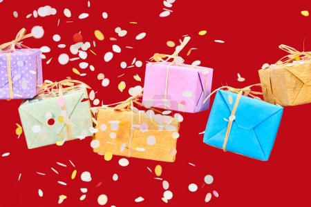 Photo for Falling confetti near colorful gifts on red - Royalty Free Image