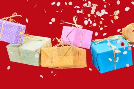 Photo pour Confettis tombant près de cadeaux colorés sur rouge - image libre de droit