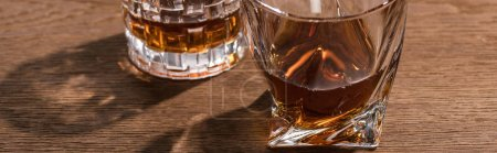 Photo for Panoramic shot of brandy in glasses on wooden table - Royalty Free Image