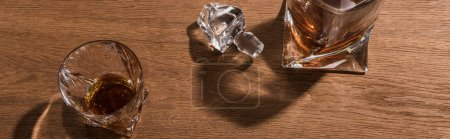Photo pour Top view of brandy in glass and decanter on wooden table, panoramic shot - image libre de droit