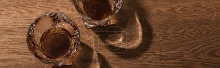 Photo for Top view of brandy in glasses on wooden table, panoramic shot - Royalty Free Image