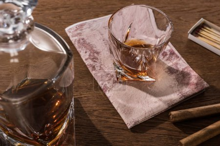 Photo pour Glass of brandy on map with decanter, cigars and matches on wooden table - image libre de droit
