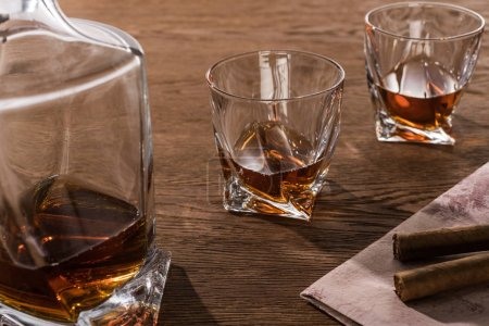 Photo pour Glasses of brandy with decanter and cigars on map on wooden table - image libre de droit