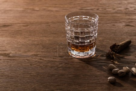 Photo for Glass of brandy with cigar and pistachios on wooden table - Royalty Free Image
