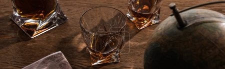 Photo pour Selective focus of brandy in glasses with globe and map on wooden table, panoramic shot - image libre de droit