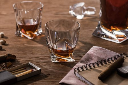 Photo pour Glasses of brandy, cigars with map and pistachios on wooden table - image libre de droit