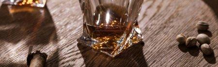 Photo pour Panoramic shot of brandy, cigar and pistachios on wooden table - image libre de droit