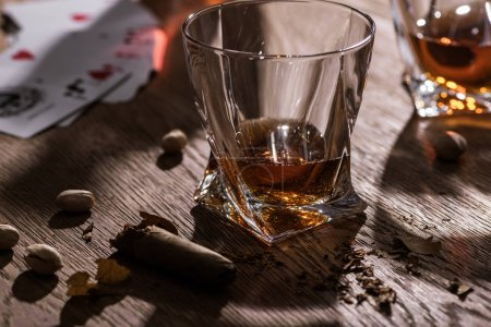 Photo for KYIV, UKRAINE - NOVEMBER 7, 2019: Glasses of brandy with cigar, pistachios and playing cards on wooden table - Royalty Free Image
