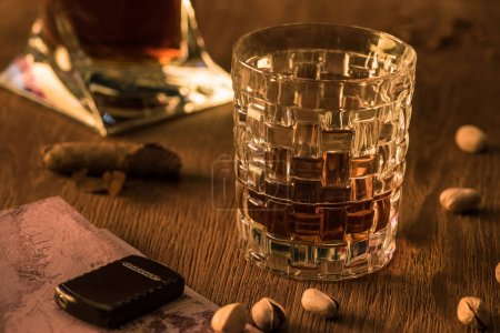 Photo pour Glass of brandy with lighter on map, pistachios and cigar on wooden table - image libre de droit