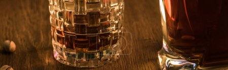 Photo pour Glass of brandy with decanter and pistachios on wooden table, panoramic shot - image libre de droit