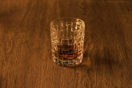 Photo for Textured glass of brandy on wooden table - Royalty Free Image