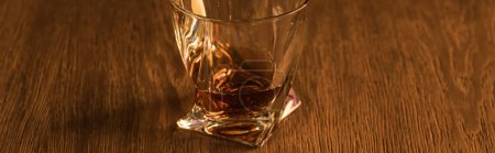 Photo for Panoramic shot of brandy in glass on wooden table - Royalty Free Image