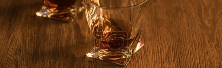 Photo for Two glasses of brandy on wooden table, panoramic shot - Royalty Free Image