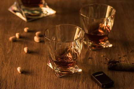 Photo for Glasses of brandy with pistachios, cigar and lighter on wooden table - Royalty Free Image