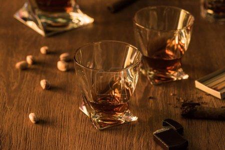 Photo pour Glasses of brandy with pistachios, cigar and lighter on wooden table - image libre de droit