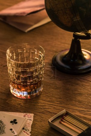 Photo pour KYIV, UKRAINE - NOVEMBER 7, 2019: Glass of brandy with matches, playing cards and globe on table - image libre de droit