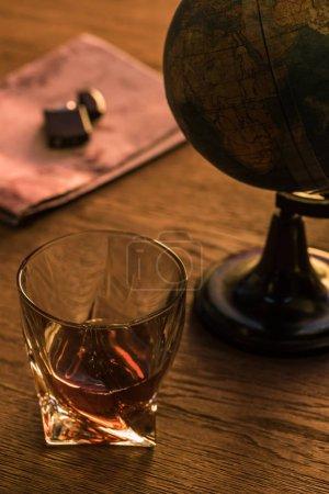 Photo pour Verre de brandy avec globe et briquet sur la carte sur table en bois - image libre de droit
