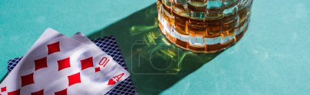 Photo for KYIV, UKRAINE - NOVEMBER 7, 2019: Glass of brandy with playing cards on green background, panoramic shot - Royalty Free Image