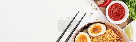 Photo for Top view of spicy ramen near fresh ingredients and chopsticks on white surface, panoramic shot - Royalty Free Image