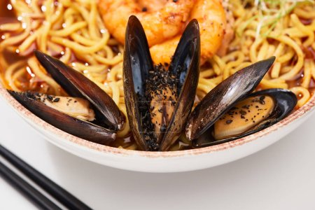 Photo for Close up view of spicy seafood ramen in bowl with mussels near chopsticks - Royalty Free Image