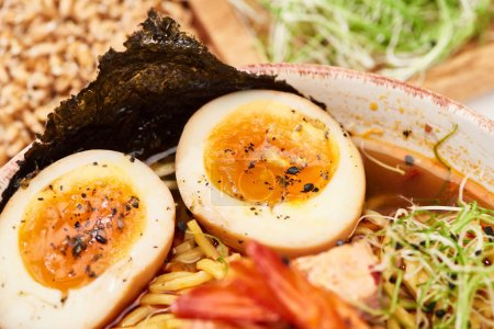 close up view of spicy seafood ramen in bowl with eggs