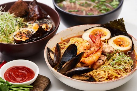 Photo for Spicy seafood and meat ramen in bowls on white surface near ketchup - Royalty Free Image