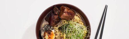 Photo for Top view of spicy meat ramen near chopsticks on white surface, panoramic shot - Royalty Free Image