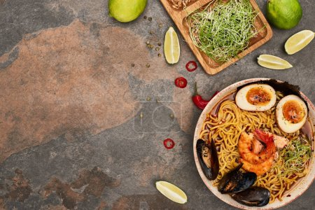 Photo for Top view of spicy seafood ramen near fresh ingredients on stone surface - Royalty Free Image