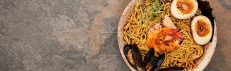 top view of spicy seafood ramen on stone surface, panoramic shot