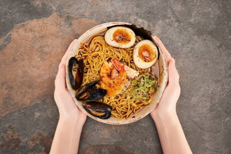 Photo pour Cropped view of woman holding bowl with spicy seafood ramen on stone surface - image libre de droit