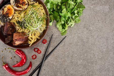 Photo for Top view of spicy meat ramen near chili pepper, parsley and chopsticks on grey concrete surface - Royalty Free Image