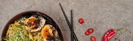 Photo for Top view of spicy meat ramen near chili pepper and chopsticks on grey concrete surface, panoramic shot - Royalty Free Image