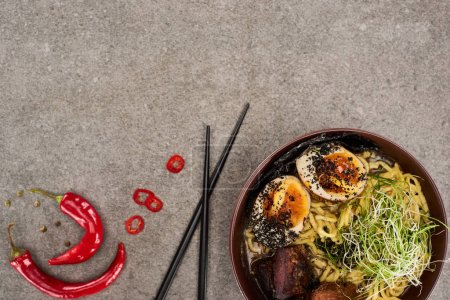 Photo for Top view of spicy meat ramen near chili pepper and chopsticks on grey concrete surface - Royalty Free Image