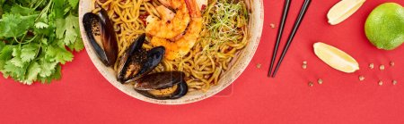 Photo for Top view of spicy seafood ramen near chopsticks, parsley and lime isolated on red, panoramic shot - Royalty Free Image