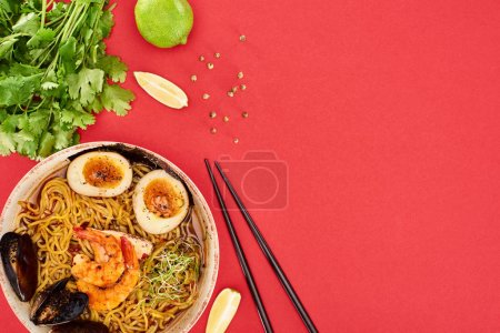 Photo for Top view of spicy seafood ramen near chopsticks, parsley and lime isolated on red - Royalty Free Image