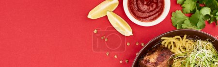 Photo for Top view of spicy meat ramen near sauce, parsley and lime isolated on red, panoramic shot - Royalty Free Image