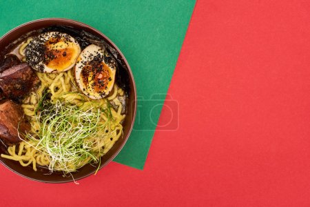 top view of spicy meat ramen on green and red surface