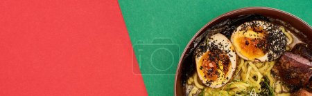top view of spicy meat ramen on green and red surface, panoramic shot