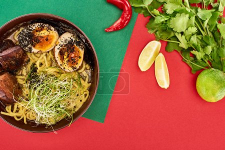 Photo for Top view of spicy meat ramen near fresh ingredients and chopsticks on green and red surface - Royalty Free Image