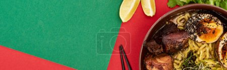 Photo for Top view of spicy meat ramen near fresh ingredients and chopsticks on green and red surface, panoramic shot - Royalty Free Image
