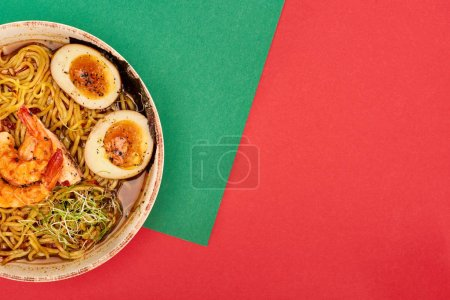 Photo for Top view of spicy seafood ramen on green and red surface - Royalty Free Image