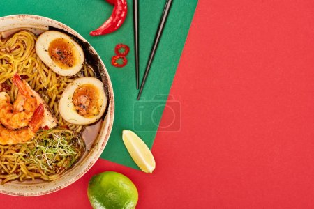 Photo pour Vue de dessus des ramen épicés de fruits de mer près des ingrédients frais et des baguettes sur la surface verte et rouge - image libre de droit