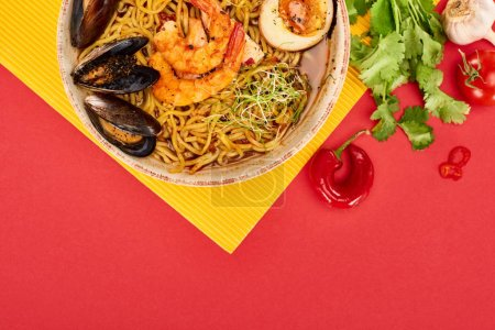 Photo for Top view of spicy seafood ramen near fresh ingredients on yellow and red surface - Royalty Free Image