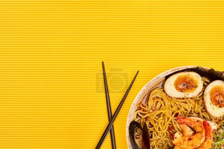 Photo for Top view of seafood ramen near chopsticks on yellow surface - Royalty Free Image